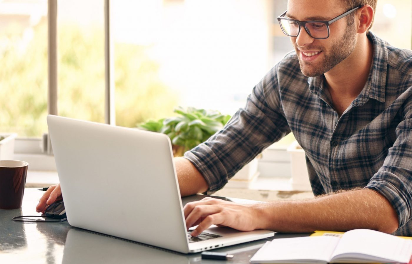 Happy young man, wearing glasses and smiling, as he works on his laptop with his cup of coffee