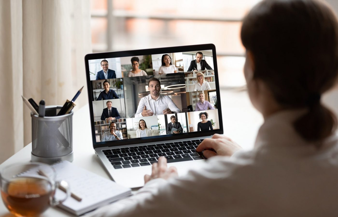 View over young woman's shoulder seated at desk looking at computer screen where there is a collage of many diverse people involved at video conference meeting