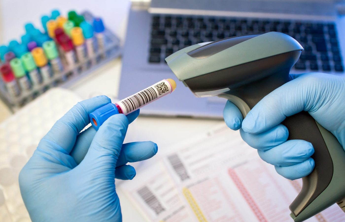 technician hands scanning bar codes on biological sample tube in the lab of blood bank