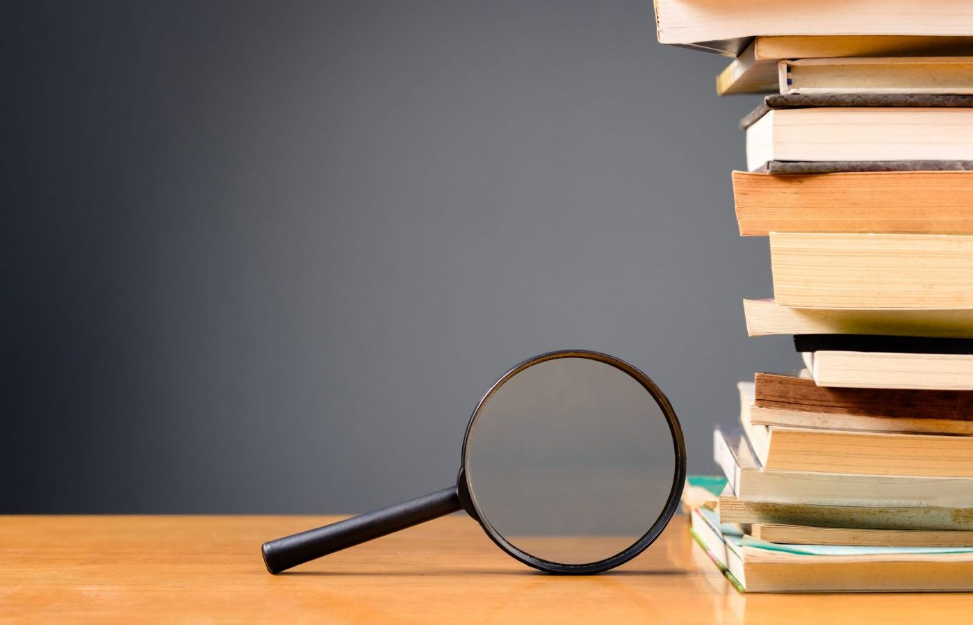 Magnifying glass and pile of books on the wood desk with copy space