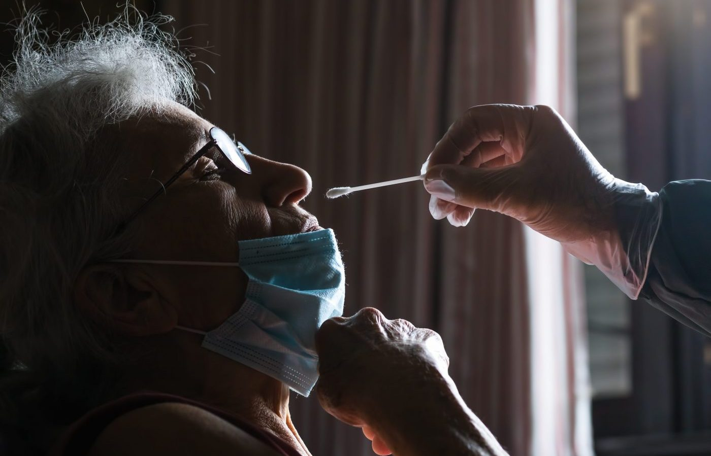 covid 19 swab nasal test performed on elderly woman at retirement home