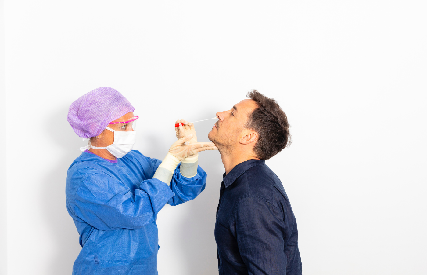man having nasal sample taken by healthcare worker in protective equipment