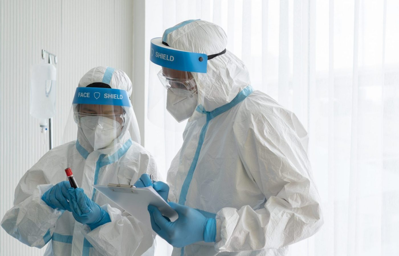 doctor and nurse in personal protective equipment showing blood test tube of patient who has covid-19 infection in hospital